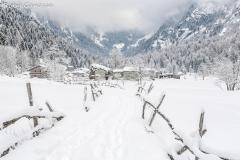 Le case di Cascina Piana in val di Mello dopo una nevicata